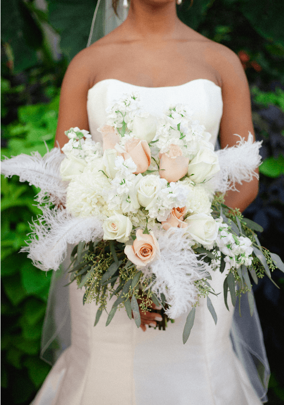 Black Bride in a strapless wedding dress holds peach and white bouquet with white feathers standing infront of greenery