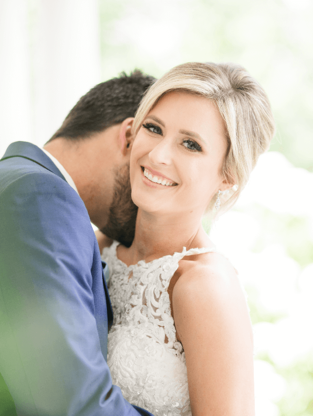 Bride smiles at the camera as groom gently kisses her neck