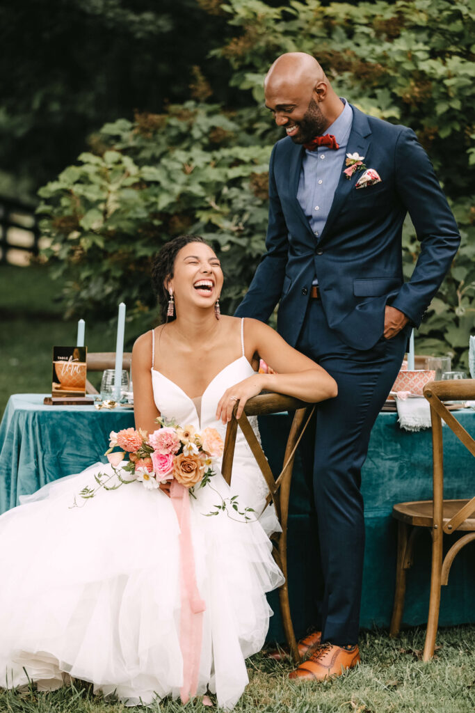 Black couple joyfully celebrates their wedding day outside in front of a beautifully style table in jewel tones. The bride wears a blush pink dress, with a garden bouquet tied with pink ribbon. The groom wears a deep blue suit, with mahogony wingtip shoes. He looks down at her smiling as she sits in a chair laughing up at him. They are incredibly happy.