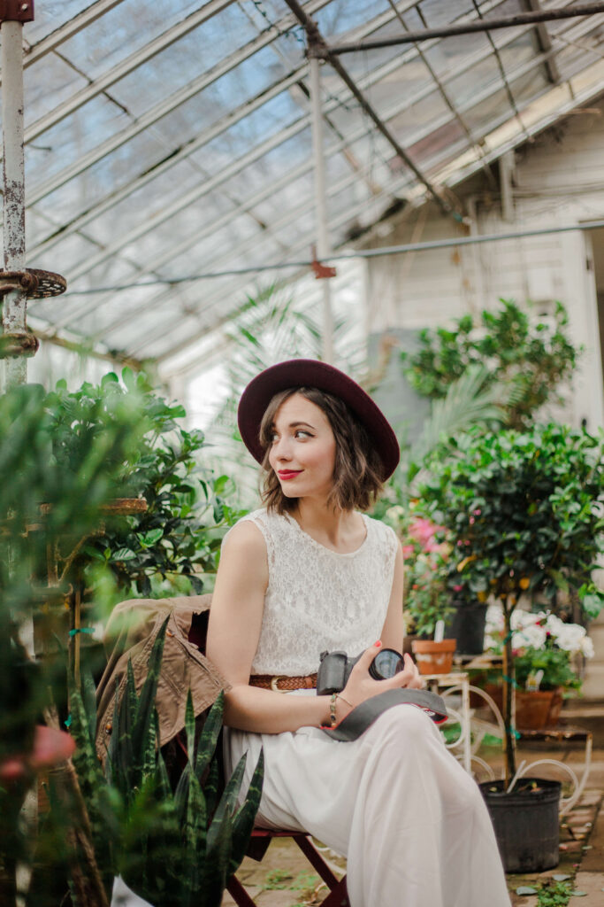 A woman with a secret sits in a green house surrounded by plants. She holds a camera, looking over her left shoulder at something that has caught her eye. A slight grin graces her face, she wears a stylish hat, gently set on the back of her head so that we can clearly see her face.