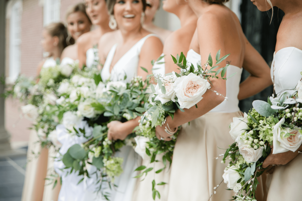 Wedding party in blush tones hold beautiful draping bouquets with greenery and blush roses. The women surround the bride, smiling at her.