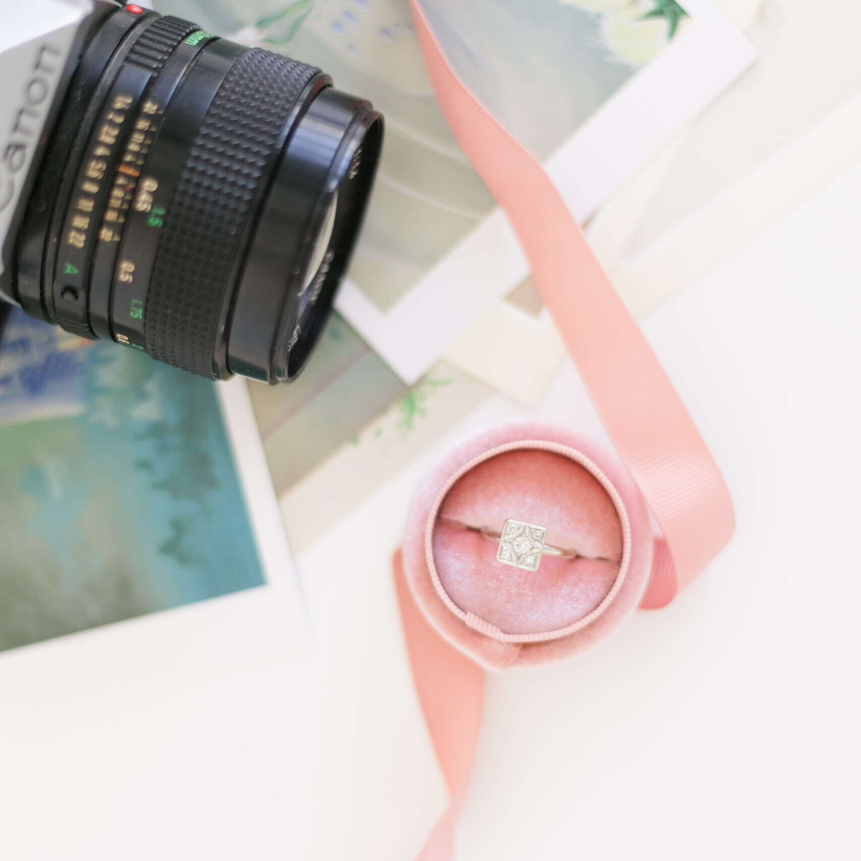 Film Camera and Engagement Ring atop images and a ribbon Veronica Sparrow Kentucky Wedding Photographer